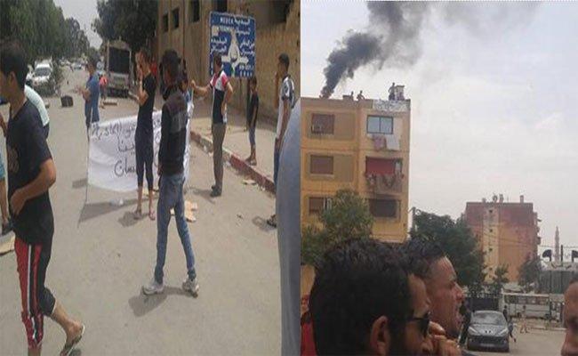 7 شباب يهددون بالانتحار الجماعي من فوق عمارة  مطالبين بسكن و تضامن محتجين معهم بإغلاق الطريق بعين الدفلى